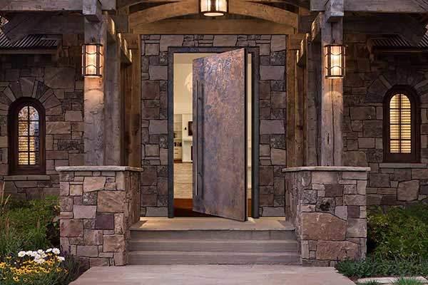 Metallic pivot door in bronze